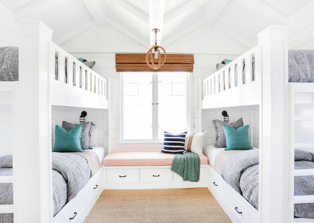 Bunk Room. White Bunk room with white bunk bed with gray bedding, turquoise decorative pillows, rope lighting, bamboo shades, window seat, sisal carpeting and shiplap walls. Bunk beds with storage under beds. #Bunkroom