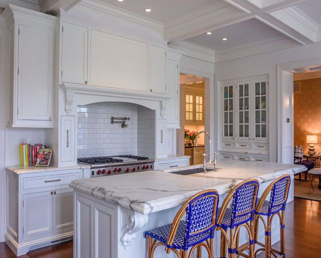 Blue kitchen counter stools. White kitchen with custom hood with white subway tile backsplash, swing warm pot filler and spice cabinets on hood. The kitchen island feautures French blue counter stools. #Kitchen #BlueCountertsool #WhiteKitchen  Via Sotheby's Homes.