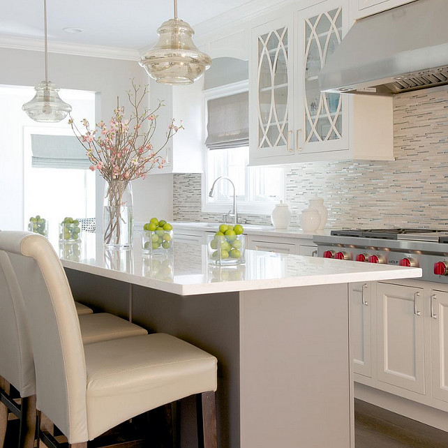 Caesarstone Frosty Carrina. Light grey island with cream color cabinets are balanced with the multi-color glass tiles. Soft hues of grey and cream are carried throughout the kitchen. #kitchen #Caesarstone #FrostyCarrina. Color Concept Theory.