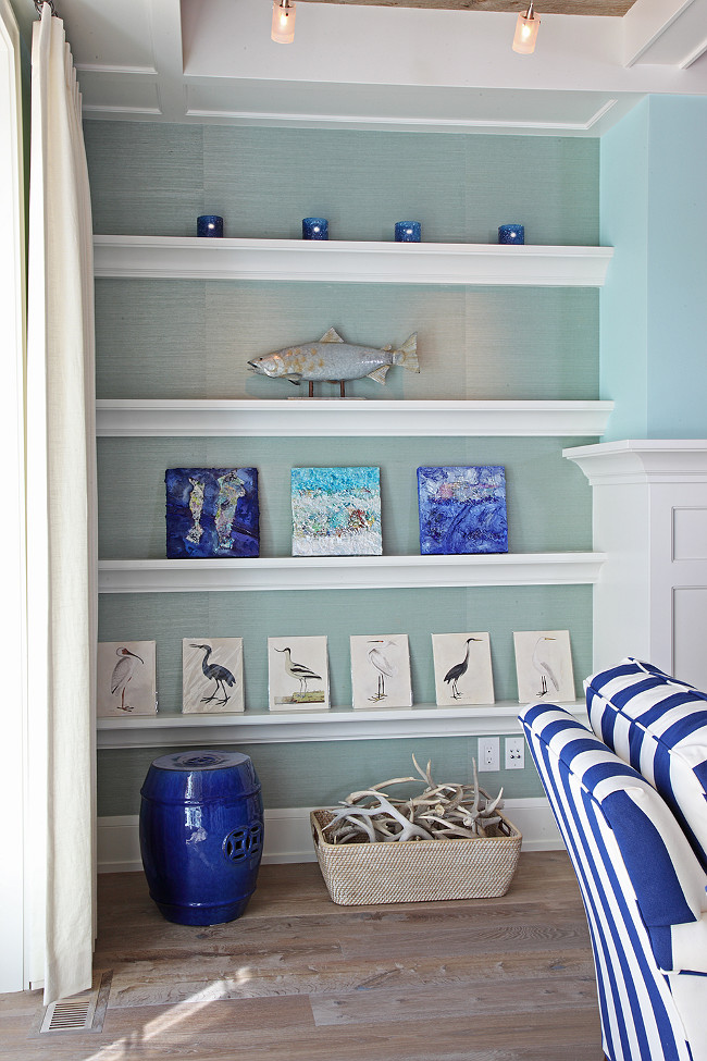 Coastal Living room with Coastal Art in fireplace bookcase. Fireplace bookcase features a turquoise wallpaper on the back wall. Leticia Little.