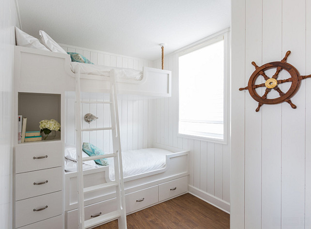 White and turquoise bunkroom. Nautical kids' bunkroom design features walls clad in vertical shiplap lined with built in bunk beds, with top bunk suspended by ropes from the ceiling, dressed in white bedding and turquoise pillows fitted with a white ladder and a built-in nook filled with books and flower stacked over a built-in dresser. #BunkRoom #WhiteBunkRoom #TurquoiseBunkRoom Laura U, Inc.