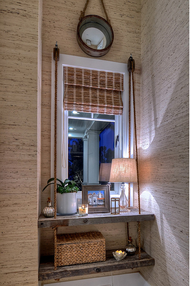 Coastal Decor Ideas. Natural wood shelves are strung from custom hemp ropes to create an eye catching design in this recessed window area. #CoastalDecor #InteriorDesignIdeas #CoastalDecorIdeas