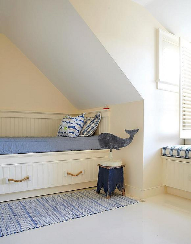 Dormer Bedroom Ideas. Dormer Bedroom Layout. Attic cottage kids' bedroom features a built-in bed clad in beadboard trim and fitted with rope pulls topped with a blue denim cushion, shark pillow and a blue gingham pillow next to a weathered blue stool atop a blue runner alongside a built-in window seat.. #Dormer #Bedroom #Attic #layout Botticelli and Pohl Architects.