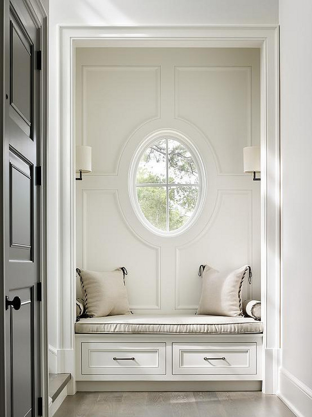 Built-in with Built in Window Seat Nook with Window. This foyer features a nook filled with a built-in window seat with drawers illuminated by oil-rubbed bronze sconces and black front door. Beth Webb Interiors.