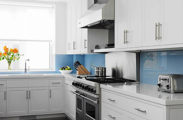 Glass Backsplash. Coastal kitchen with blue glass backsplash. White & blue kitchen design with crisp white kitchen cabinets with white quartz countertops and blue backsplash. #kitchen #GlassBacksplash John B Murray Architect.