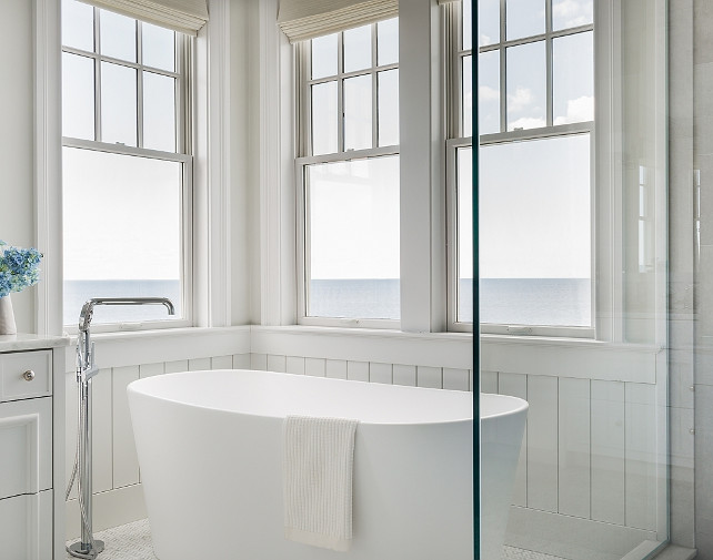 Master bathroom boasts walls clad in vertical shiplap framing windows dressed in cream roman shades situated over a freestanding oval tub and a floor mount spigot tub filler placed next to a seamless glass shower. #Bathroom #Tub #FreestandingBath #FloorMountTubFiller #SpigotTubFiller