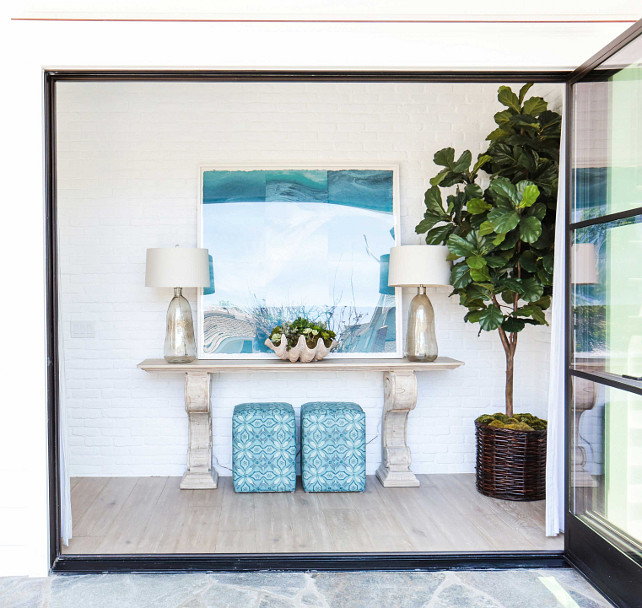 Foyer. Beach house front foyer design. Beach house coastal foyer. Folding doors open to a coastal foyer featuring a pair of turquoise stools tucked under a carved console table. Beautiful blown glass lamps and a large clam shell bowl together with a turquoise art tie this space together. Fiddle leaf fig plant. #Foyer #Turquoise #Coastal #CoastalInteriors Blackband Design.