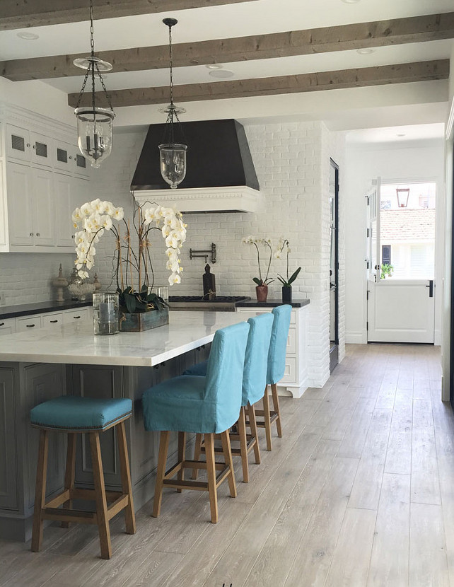 Bright White Kitchen with plank hardwood floors. Bright White Kitchen with plank hardwood floors, marble counters, white brick walls, beamed ceiling and turqupise stools. #Kitchen #BrightWhiteKitchen #WhiteKitchen Blackband Design.