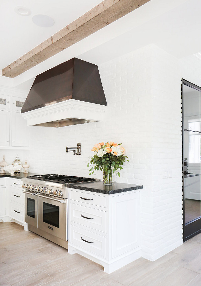 White kitchen boasts a ceiling clad in wood beams over a black and white kitchen hood which stands over a swing arm pot filler and a high end stainless steel stove. Kitchen with white cabinets paired with black marble countertops and a white brick wall backsplash alongside a gray wood floor. White Brick Kitchen Wall and Backsplash Blackband Design.
