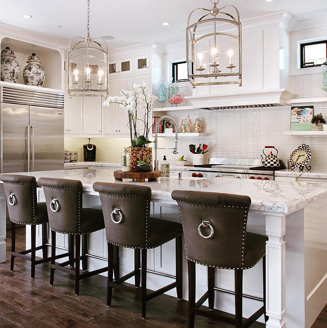 White kitchen love! White kitchen island stools. Stools were purchased from Crate & Barrel, we had them custom re-upholstered. We also added the nail heads and ring hardware to dress them up a bit! The pendants are from Visual Comfort. #WhiteKitchen Spinnaker Development.