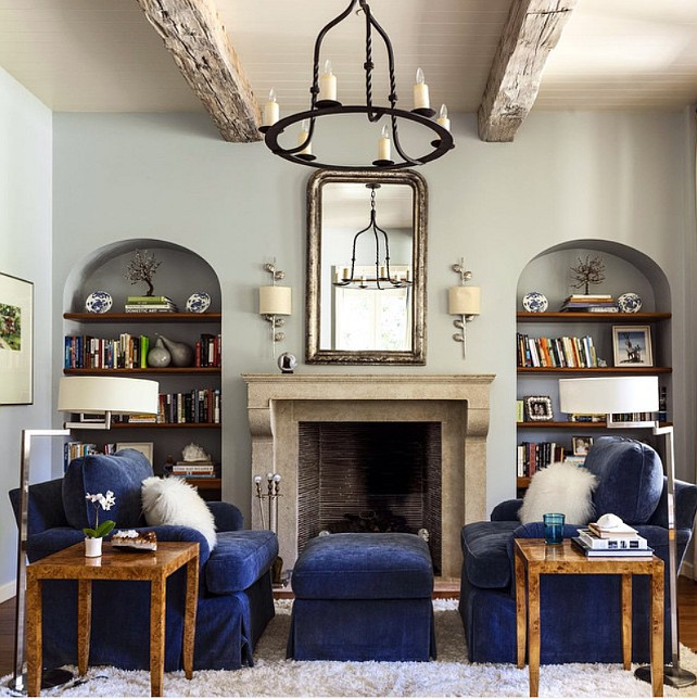 Bookshelves on both sides of fireplace. Living room with Bookshelves on both sides of fireplace. Bookshelves on both sides of fireplace, navy velvet couches facing each other and grey walls. Collins Interiors.