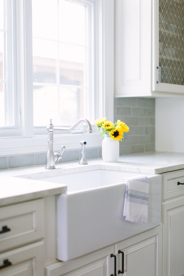Farmhouse Sink. Kitchen with white farmhouse sink. Kitchen features white raised panel cabinets adorned with oil rubbed bronze pulls paired with white marble countertops and a blue beveled subway tiled backsplash. A farmhouse sink stands under a hook and spout faucet placed under windows flanked by cabinets fitted with metal lattice doors. #Kitchen #FarmhouseSink #Sink #KitchenSink #ApronSink  Kate Marker Interiors.