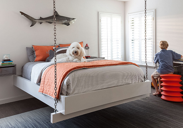 Boys Bedroom. Hanging bed in boys bedroom. Boy's bedroom features a shark sculpture over a hanging bed suspended from the ceiling by chains dressed in gray and orange bedding flanked by floating industrial metal nightstands. #BoysBedroom #HangingBed Jean Liu Design.