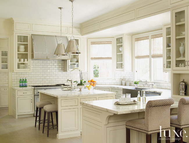Kitchen. Classic Kitchen. This classic kitchen kitchen includes custom barstools (foreground) covered in Nobilis fabric, which pull up to a honed Calacatta marble countertop. Custom cabinetry continues the room's sophisticated white-on-white palette. #Kitchen #Classic Courtney Hill Fertitta.