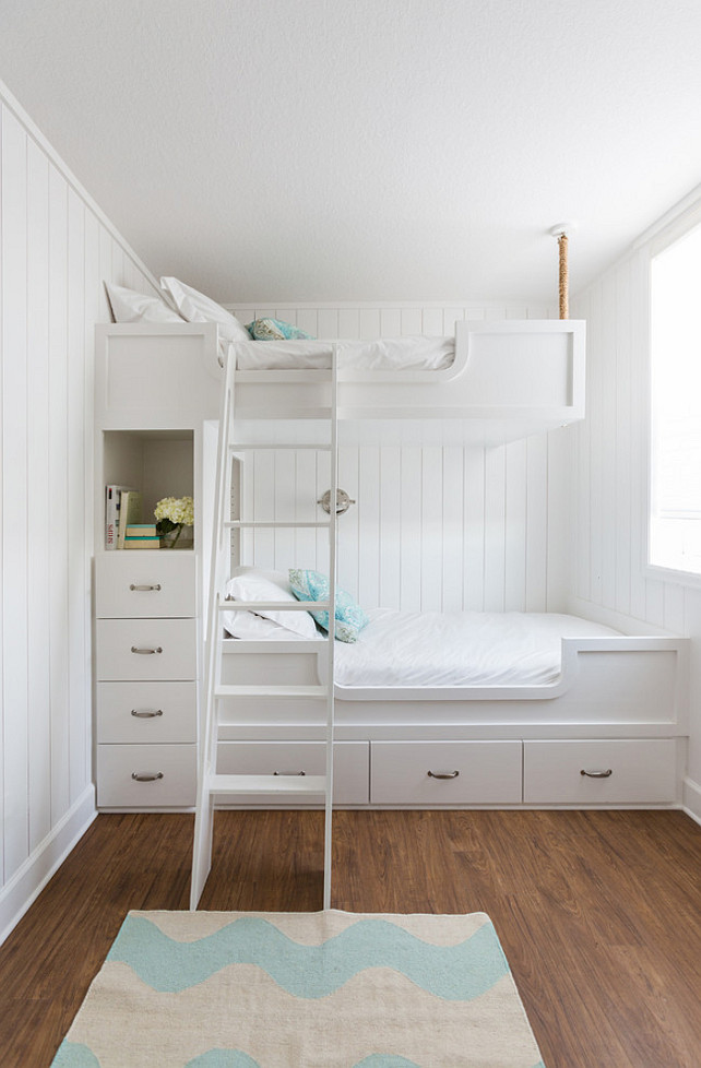 Nautical kids' bedroom design features walls clad in vertical shiplap lined with built in bunk beds, with top bunk suspended by ropes from the ceiling, dressed in white bedding and turquoise pillows fitted with a white ladder and a built-in nook filled with books and flower stacked over a built-in dresser. Laura U, Inc.