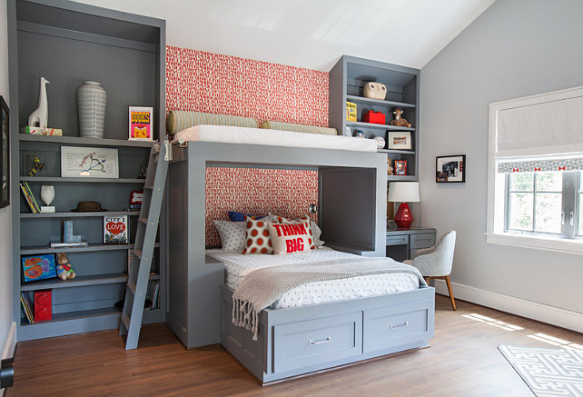 Built-in Bed with reading lounge on top. Gray kid's bedroom features a wall clad in red alphabet wallpaper lined with a gray bed dressed in gray polka dot bedding situated under an overhead reading nook accessible by a gray ladder. Contemporary boy's bedroom features a built-in bed flanked by floor to ceiling gray bookcases with the right bookcase fitted with a gray desk and a striped task chair. Wallpaper is Alexander Girard Alphabet wallpaper manufactured by Maharam. Laura U, Inc.