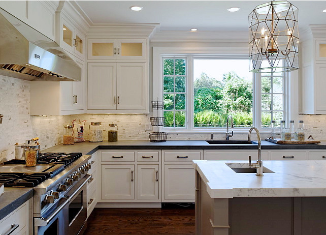 Kitchen Decor Ideas. Beautiful kitchen with white perimeter cabinets paired with honed black countertops and white marble backsplash. Worlds Away Mariah Pendant over gray kitchen island with white marble countertop with prep sink accented with gooseneck faucet. #Kitchen #KitchenDecor Blue Water Home Builders.