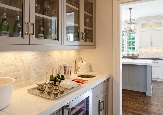 Butlers pantry. Gray butlers pantry. Butler's pantry features glass-front upper cabinets and gray lower cabinets paired with statuary marble countertop and white marble linear tile backsplash. #Butlerspantry #statuarymarblecountertop #lineartilebacksplash Blue Water Home Builders.