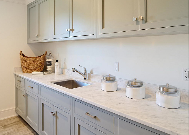Laundry Room cabinet and countertop. Laundry room with gray cabinets paired with carrera marble countertops. Laundry room features square sink as well as vintage canisters. #LaundryRoom #Countertop #Cabinet Blue Water Home Builders.