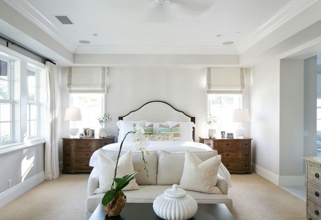 Bedroom. Master bedroom. Bedroom with settee. Lovely bedroom features arched bed dressed in soft white bedding and gray and mint green striped pillows flanked by traditional nightstands placed under windows dressed in gray grosgrain roman shades as well as a linen loveseat accented with damask pillows and espresso coffee table placed at the foot of the bed. #Bedroom #Settee