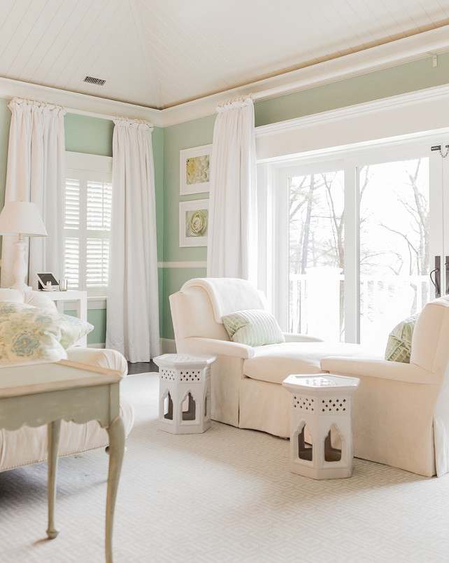 Mint Green. Mint green bedroom boasts white tongue and groove vaulted ceilings over large windows and sliding patio doors dressed in simple white drapes alongside mint green walls accented with chair rail. The bedroom features an ivory tete a tete chaise armchair topped with mint green striped pillows beside a pair of white Moroccan garden stools atop an ivory Greek key rug layered over hardwood floors. #MintGreen #Bedroom Brookes and Hill Custom Builders.