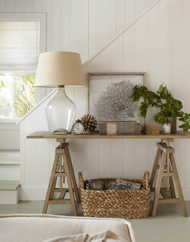 Foyer Decor Coastal Cottage Foyer. Cottage foyer is filled with a seagrass basket filled with magazines tucked under wood sawhorse table with smoke gray glass lamp, framed sea fan #Cottage #Foyer Jenny Wolf Interiors