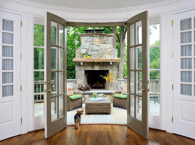 Patio Stone Fireplace and Hearth. French Doors open to a patio with natural stone fireplace and hearth. French doors open to a patio filled with a stone fireplace with hearth alongside a pair of wicker chairs with green cushions facing each other across from a wicker ottoman with glass top. #Patio #StoneFireplace #Hearth Erica Burns Interiors.