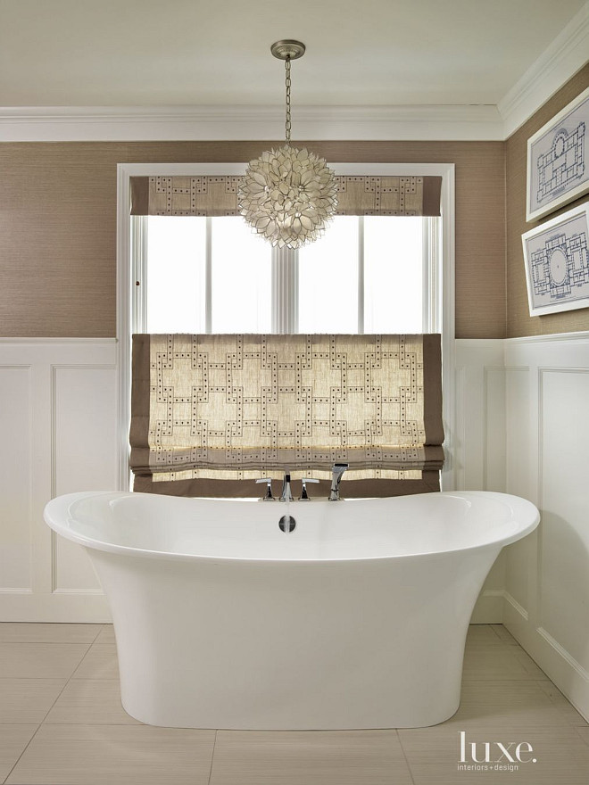 Master Bathroom Ideas. The master bathroom is clad in new wainscoting and Phillip Jeffries wallpaper. Custom window treatments lend warmth to the room; the Worlds Away Venus Capiz Pendant light adds elegance to this bathroom. #MasterBathroom GR Interiors.