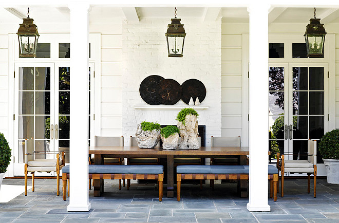 Covered Patio. Gorgeous covered patio with a pair of French doors with transom windows flanking a white brick fireplace. The outdoor patio features an iron based wood topped dining table paired with wooden benches with blue seats and upholstered side chairs. The dining table is topped with three wooden planters with green trailing plants. Three outdoor lanterns hang from the covered patios ceiling over the dining table. Traditional style planters with round boxwoods stand either side of the dining area. The outdoor dining area is finished with a flagstone patio. #CoveredPatio #Patio #Backyard Jeffrey Alan Marks.