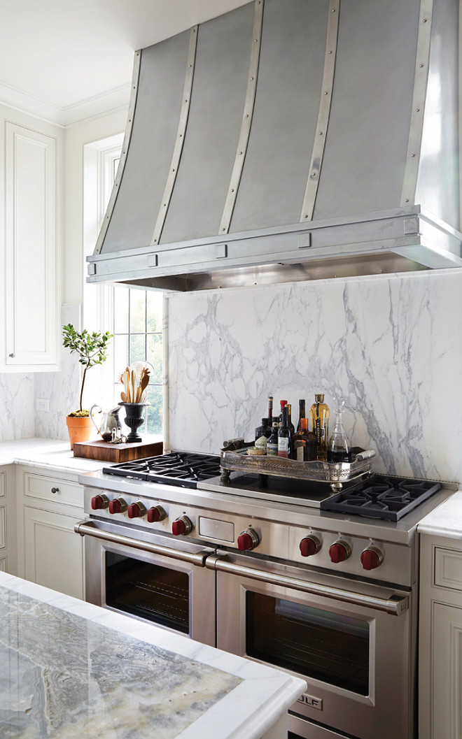 Kitchen Marble Slab Backsplash. Marble Slab Backsplash Behind Range. White Marble Slab Backsplash. Kitchen with a zinc French kitchen hood is placed above a marble cooktop backsplash and Wolf Range flanked by windows. #Kitchen #Marble #Slab #Backsplash Cyndy Cantley. Birmingham Home and Garden.