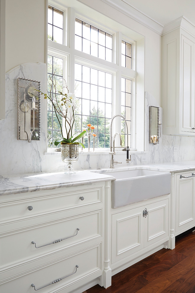 Kitchen Sink Windows and Sconces. Kitchen with sconces. Kitchen farmhouse sink, industrial faucet and mirrored sconces. Exquisite kitchen features creamy white cabinets paired with grey and white marble countertops and a curved marble backsplash lined with mirrored wall sconces. A farmhouse sink and pull out faucet stands below windows. #Kitchen #Sconces #FarmhouseSink Cyndy Cantley.
