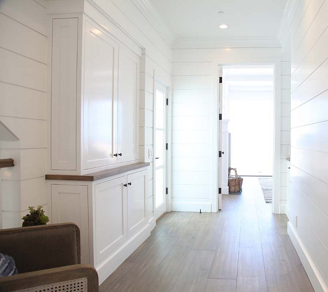 Stairway Landing with shiplap walls, graywashed hardwood floors and built-in cabinet. Graystone Custom Builders.
