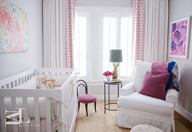 Purple and gray nursery features walls painted cool grey lined with an abstract art piece over a white crib accented with white bumpers with rope ties alongside a black kid's bentwood chair accented with a purple chevron cushion atop a seagrass rug. Chic girl's nursery boasts a white slipcovered chair with rolled-arms adorned with a purple chevron pillow next to a round metal accent table topped with a gold bunny lamp placed under a purple and pink abstract art piece a windows dressed in white and pink curtains.