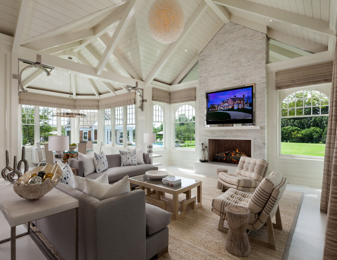 Sunroom. Ultimate sunroom in a Hamptons house with stunning architectural details, stone fireplace, beached hardwood floors and Vaulted Ceiling with exposed v shaped trusses. #Sunroom #Ceiling #VaultedCeiling #exposed #trusses Sotheby's Homes.