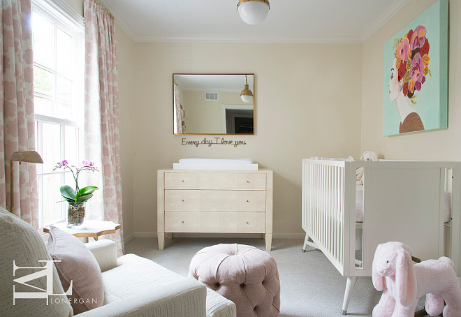 "Cream and pink nursery features a turquoise art piece over a Dwell Studio Mid Century French White Crib facing a window dressed in pink flower drapes. A three drawer cream dresser as changing table topped with a changing tray situated below a an ""Everyday I Love You"" sign and brass mirror illuminated by an antique brass Hicks Pendant. Meg Lonergan."