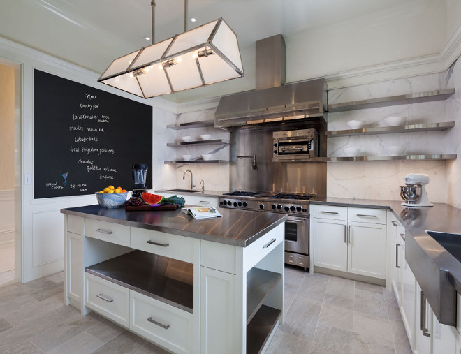 Modern KItchen with Chalk Board. This modern kitchen features a chalk board, marble slab backsplash, stainless steel countertop and floating shelves on both sides of rangle hood. #Modern #Kitchen #ChalkBoard #FloatingShelves #StainlesssteelCounbtertop Sotheby's Homes.