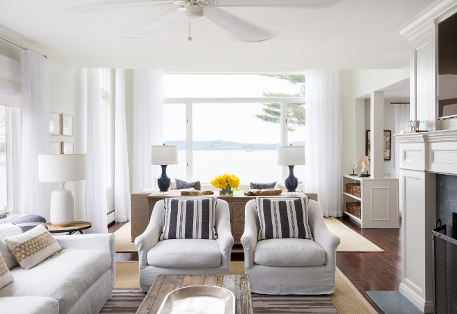 Living Room Decor Ideas. The living space boasts a white sofa flanked by round industrial end tables next to a pair of white slipcovered chairs adorned with blue and grey striped pillows facing a wood and chrome bench coffee table atop a striped rug layered over a bound sisal rug. #LivingRoom #Decor #Interiors Chango & Co.