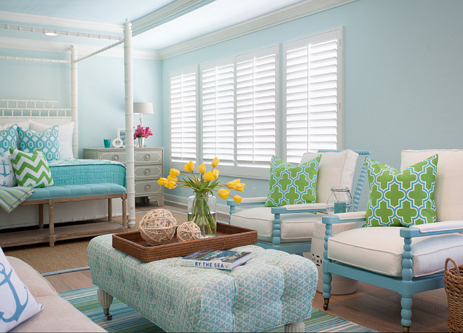 Turquoise Bedroom sitting area is filled with a pair of blue spindle chairs lined with green and blue Moroccan tile pillows facing a blue tufted ottoman on caster legs atop a turquoise and green striped rug. #Turquoise #Bedroom AGK Design Studio.