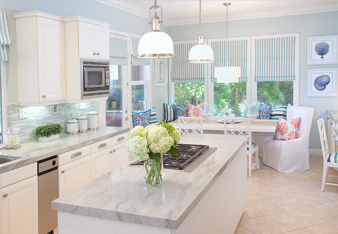 Coastal Kitchen. White and blue cottage kitchen features white cabinets paired with quartzite countertops and blue glass tiled backsplash. #Coastal #Kitchen #BlueglassBacksplash #Quartzite AGK Design Studio.
