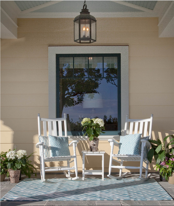 Beach house front porch with white rocking chairs, blue turquoise pillows, light blue outdoor rug and a lantern pendant hung from the blue ceiling. #porch Kim Grant Design Inc.