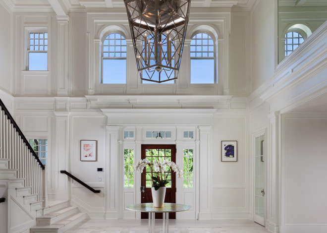 Benjamin Moore China White. This impressive two story foyer is painted in Benjamin Moore China White. Notice the detailed wainscoted staircase and ceiling. #BenjaminMooreChinaWhite #Foyer #Windows