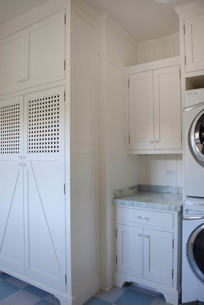 Laundry Room. Main Level Laundry Room. This Main Level Laundry room features white cabinets paired with a gray quartzite countertop and a shiplap backsplash alongside a blue checkered tiled floor. #LaundryRoom Kim Grant Design Inc.