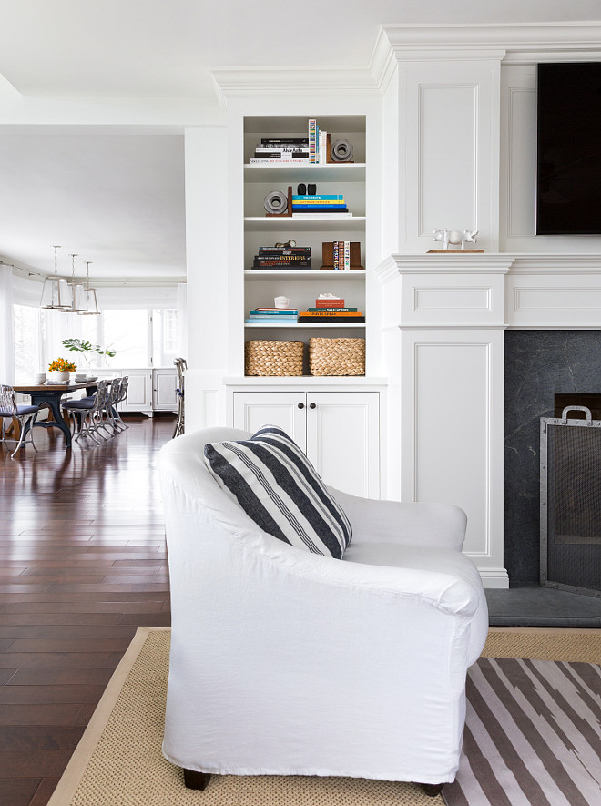 Beautiful fireplace with soapstone surround. The cabinet is painted in White Dove by Benjamin Moore. A swhite slipcovered chair features a dark gray striped pillow is from Ralf Lauren Home. Fireplace screen is from Pottery Barn. #Livingroom #Fireplace #Cabinet #Chair