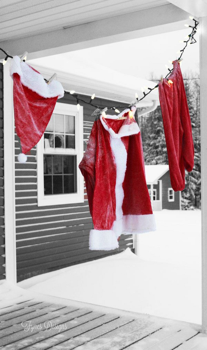 Make the kids wonder during this Christmas. Hang on the porch a Christmas Santa Suit from a string of lights Outdoor Christmas decoration. Via FYNES DESIGNS.
