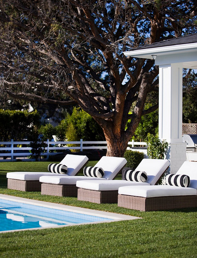 Pool Lounges with white cushion and black and white lumbar pillows.
