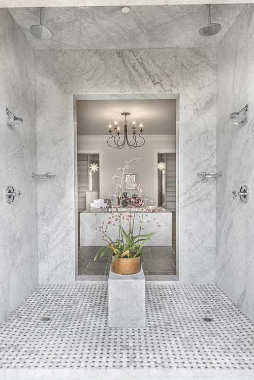 Shower. The walk-in shower features marble slab walls and marble basketweave mosaic tile floors.