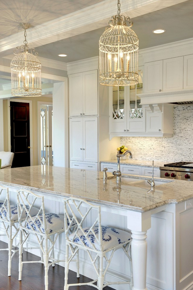 White kitchen boasts a pair of white birdcage chandeliers hanging over a white kitchen island accented with turned legs topped with gray and white granite countertops framing a white porcelain sink lined with white bamboo counter stools. Glass-front kitchen cabinets with eclipse mullion doors flank a white kitchen hood with corbels over a white and gray mosaic tiled backsplash over a high-end stainless steel stove beside full height pantry cabinets. #kitchen Stonewood Inc..jpg