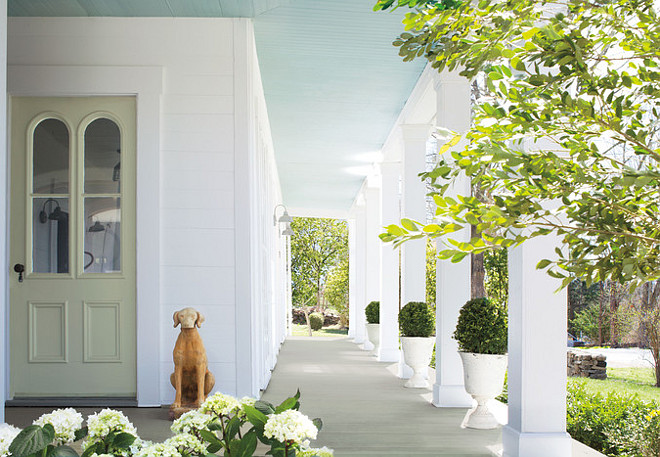 Blue Porch Ceiling Paint Color. Blue is the go-to hue for a patio or porch. Benjamin Moore's Aura, Low Lustre, Harbor Haze 2136-60 (ceiling), Aura, Low Lustre, White Diamond OC-61 (siding), Grand Entrance, Satin, Tree Moss 508 (door) #Blue #Porch #Ceiling #PaintColor Via Bright Nest.