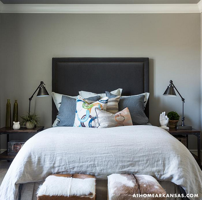 Masculine bedroom with gray walls highlighting a charcoal gray velvet headboard on queen bed layered with linen euro shams and gray matelasse pillows with a cluster of abstract pillows in front flanked by iron and wood nightstands topped with adjustable bronze task lamps with a pair of cowhide cubes at the foot of the bed. At Home in Arkansas.