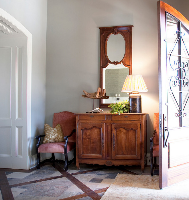 Farmhouse Foyer. Farmhouse foyer with antler arched door filagree footed commode footed console interior light gray walls pink upholstery recessed panel cabinet doors table lamp tile floor wainscoting wood mirror frame wrought iron #Farmhouse #FarmhouseInteriors #Foyer Allard Ward Architects.
